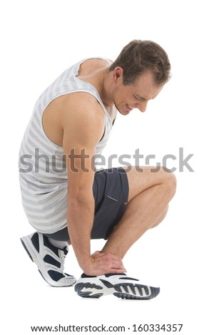 Sportsman feeling pain in his foot. Sitting and touching his foot  - stock photo