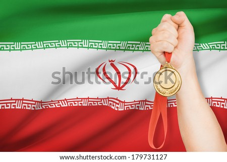 Sportsman holding gold medal with flag on background - Islamic Republic of Iran - stock photo