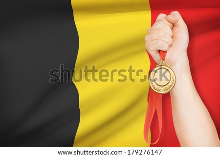 Sportsman holding gold medal with flag on background - Kingdom of Belgium - stock photo