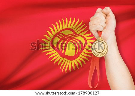 Sportsman holding gold medal with flag on background - Kyrgyzstan - stock photo