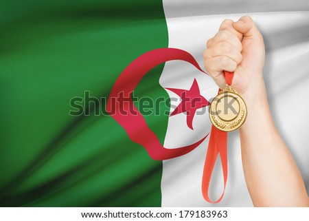 Sportsman holding gold medal with flag on background - People's Democratic Republic of Algeria - stock photo