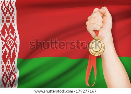 Sportsman holding gold medal with flag on background - Republic of Belarus - stock photo
