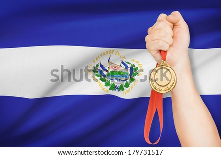 Sportsman holding gold medal with flag on background - Republic of El Salvador - stock photo