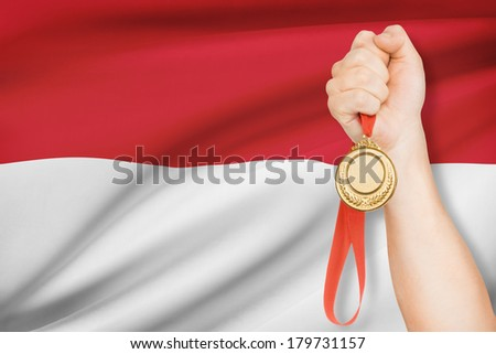 Sportsman holding gold medal with flag on background - Republic of Indonesia - stock photo