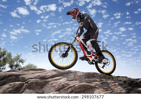 Sportsman in sportswear on a mountain bike rides on the stones in the extreme style of downhill - stock photo