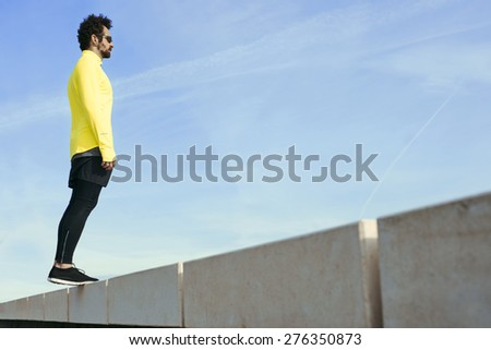 Sportsman in yellow wind breaker taking break with crossed hands standing on sky background. Fit man resting after workout outdoors, runner resting after fitness training. - stock photo