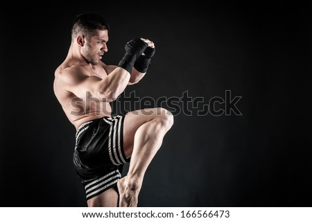 Sportsman kick boxer fighting against black background.  - stock photo