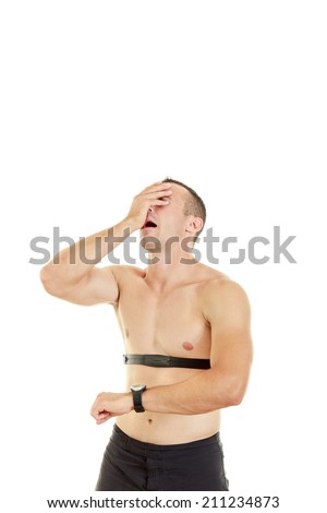 Sportsman measuring pulse and heart beat at home with stress expression due to bad results - stock photo