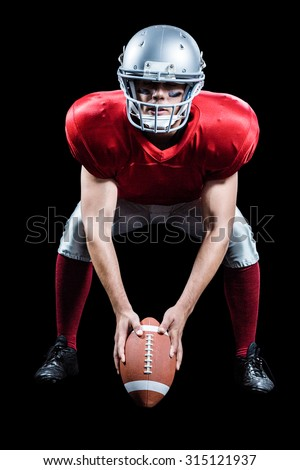 Sportsman placing American football while playing against black background - stock photo