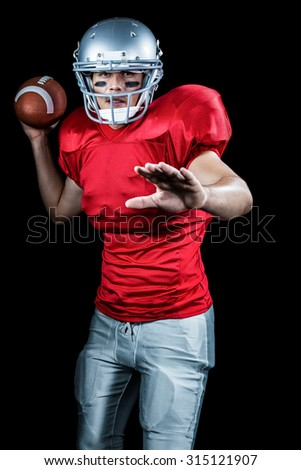 Sportsman throwing American football while playing against black background - stock photo