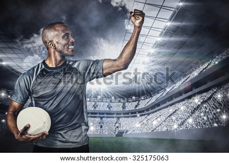 Sportsman with clenched fist holding rugby ball after victory against football stadium with fans in white - stock photo