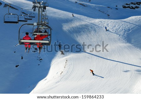 Sportsmen are being transported with a chair lift up the snowy slope. Another skiers are sliding down the snow-covered hill in the winter Pyrenees. - stock photo