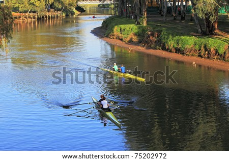 Sportsmen-oarsmen on kayaks floating down the river in the sunset - stock photo