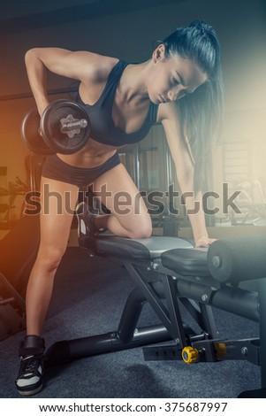 sportswoman do exercises with dumbbells - stock photo