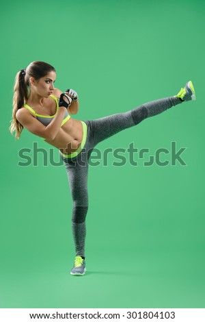 sportswoman in training, making side kick, her hands in front of chest; sportswoman on a green background in a gray sports suit. - stock photo