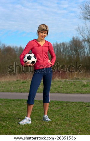 Sportswoman standing  outdoors with a ball. - stock photo