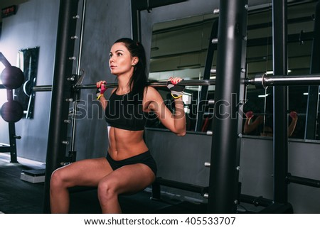 sportsy woman doing squats with a barbell in Smith machine  - stock photo