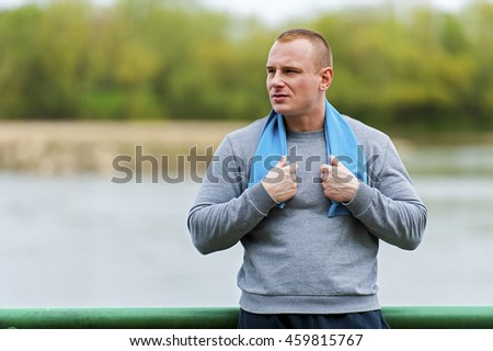 Sporty active man resting after workout with towel on shoulders. - stock photo
