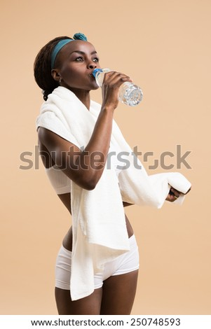 Sporty african woman drinking water from bottle. Fit sexy body - stock photo