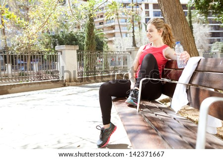 Sporty and attractive young woman sitting down on a wooden bench in the city, taking a break from exercising and drinking mineral water during a sunny morning, smiling. - stock photo