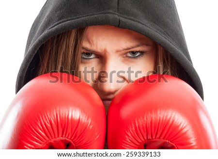 Sporty and beautiful female boxer wearing red boxing gloves and black hood - stock photo