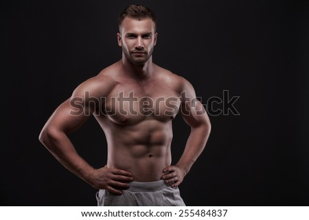 Sporty and healthy muscular man isolated on black background - stock photo