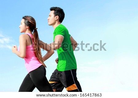 Sporty asian young couple running outside together - stock photo