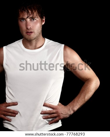 sporty athlete man portrait on black background. Young muscular fit fitness man isolated on black background. Caucasian model. - stock photo