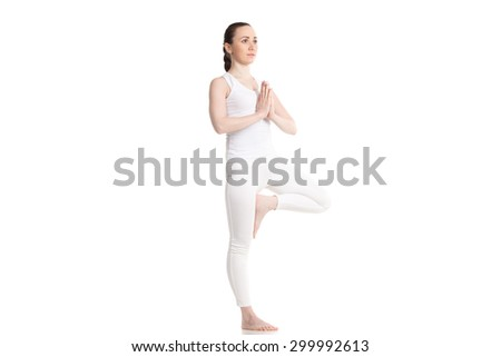 Sporty attractive young woman in white sportswear doing yoga Tree pose, standing on one leg, hands in Namaste, prayer gesture, part of large photo series, isolated, full length, three-quarters view - stock photo
