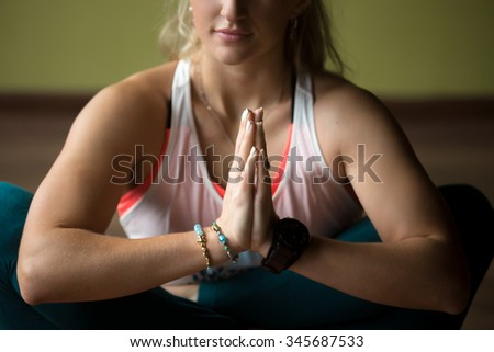 Sporty beautiful blond young woman in sportswear working out indoors, doing variation of Pranama Garbha Pindasana - Womb Embryo Pose with Namaste, horizontal image, close-up of hands - stock photo