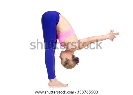 Sporty beautiful young blond woman doing Standing Forward Bend, Uttanasana pose variation, stretching shoulders, spine and legs, studio full length isolated shot on white background, profile view - stock photo