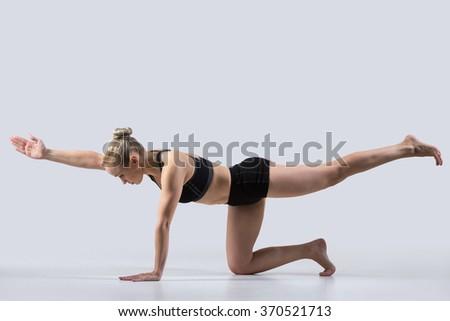 Sporty beautiful young woman practicing yoga, doing balance exercise bird dog, kneeling opposite arm and leg extension, asana sunbird (chakravakasana), working out wearing black sportswear, studio - stock photo