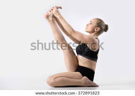 Sporty beautiful young woman practicing yoga, doing Heron pose, Krounchasana, for strength and flexibility in the joints and muscles of the legs, working out wearing black sportswear, studio - stock photo