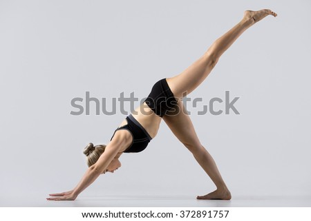 Sporty beautiful young woman practicing yoga, doing one-legged downward facing dog pose, eka pada adho mukha svanasana, working out wearing black sportswear, studio, full length, side view - stock photo
