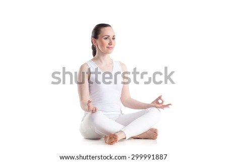 Sporty beautiful young woman practicing yoga, Sitting in Easy (Decent, Pleasant Pose), Sukhasana, asana for meditation, pranayama, breathing, studio full length isolated shot, three-quarters view - stock photo