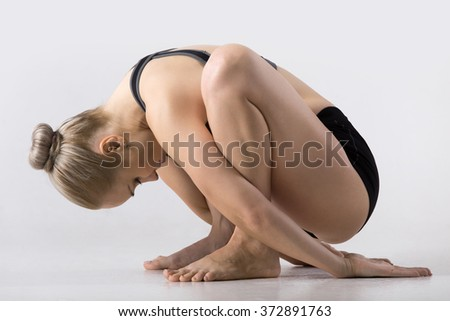 Sporty beautiful young woman practicing yoga, sitting in squat, variation of Garland Pose, Malasana with forward bend, working out wearing black sportswear, studio - stock photo