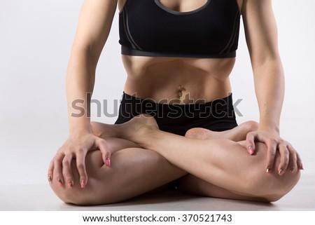 Sporty beautiful young woman practicing yoga, sitting with crossed legs, in Padmasana, Lotus Posture, performing Upward Abdominal Lock, Uddiyana Bandha, close-up, studio - stock photo