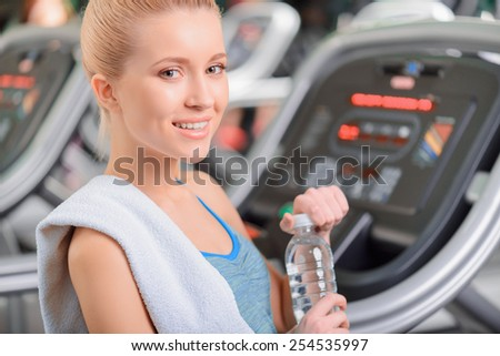 Sporty beauty. Attractive young woman in sports clothing holding bottle with water and smiling while standing in health club - stock photo