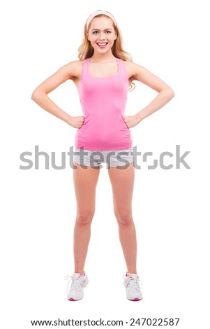 Sporty beauty. Full length of beautiful pin-up blond hair woman in pink shirt holding hands on hip and smiling while standing isolated on white background - stock photo