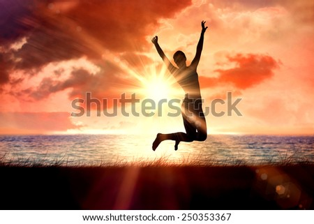 Sporty blonde jumping with arms out against sunrise over magical sea - stock photo