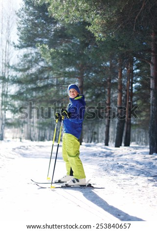 Sporty boy skiing in the forest, sunny winter day - stock photo