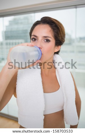 Sporty calm brunette drinking from water bottle in bright room - stock photo