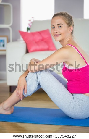 Sporty cheerful blonde model sitting on blue exercise mat in bright living room - stock photo
