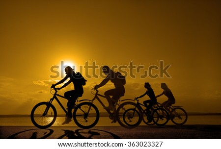 Sporty company friends on bicycles outdoors against sunset Silhouette five 5 cyclist going along shoreline coast Reflection sun on water Sport in Nature background Group of people. Empty Copy Space  - stock photo