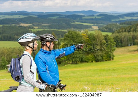 Sporty cyclist couple, man pointing to beautiful landscape - stock photo