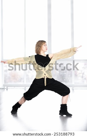 Sporty dancer woman in class exercising, warming up in yoga asana, standing in lunge - stock photo