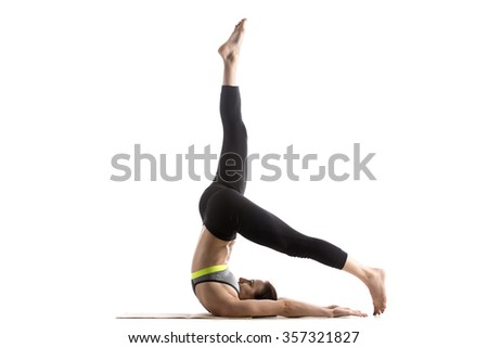 Sporty fit beautiful young woman in sportswear bra and black pants working out, doing One-legged Supported Shoulderstand pose, Control Balance Exercise, studio full length, isolated, white background - stock photo