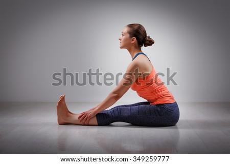 Sporty fit woman practices Ashtanga Vinyasa yoga back bending asana Paschimottanasana - seated forward bend beginner variation - stock photo