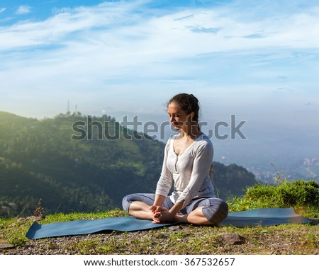 Sporty fit woman practices yoga asana Baddha Konasana - bound angle pose outdoors in HImalayas mountains in the morning with sky. Himachal Pradesh, India - stock photo