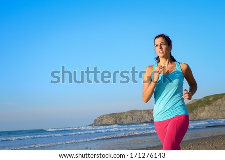 Sporty fitness woman on running workout at the beach on summer. Female healthy athlete training and exercising outdoors. - stock photo